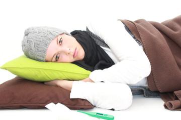 junge Frau liegt mit Erkältung im Bett