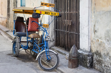 Street in Havana with an  old bicycle and shabby buildings