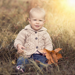 Playful child sitting on grass with maple leaves in fall season.