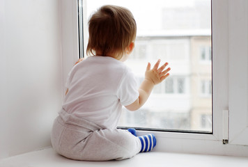lovely baby age of 1 year looks out of window in winter