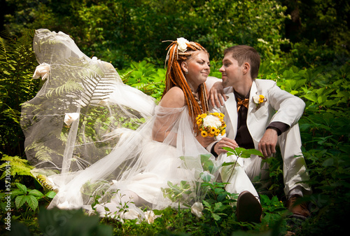 woman with dreadlocks hugging with groom in forest