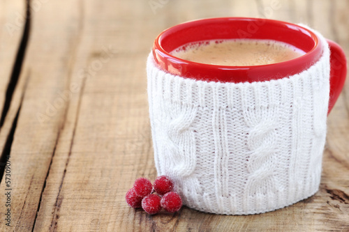 Christmas concept - red cup of coffee in knitted cup holder