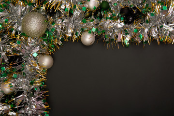 Christmas tinsel is on black background.