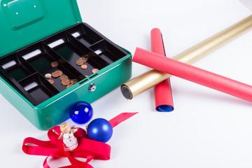 Schleifen und Geschenkpapier vor fast leerer Geldkassette