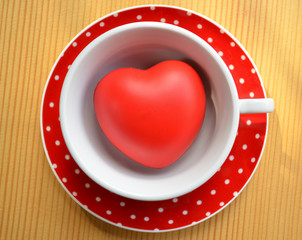 Red polka dot cup of coffee with heart on wooden background