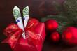 Geldgeschenk mit roten Weihnachtskugeln auf dunklem Holz