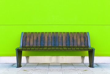 Stylish bench against green wall