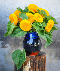 Decorative sunflowers are in a ceramic milk jug