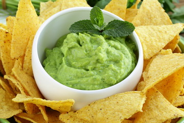 cup with guacamole and corn chips