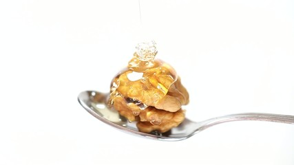 Honey and nuts on spoon close up
