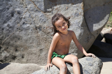 Niña sentada en una roca sonriendo