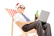 Mature businessman with santa hat on a chair, drinking beer