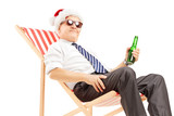 Smiling mature businessman with santa hat sitting on a chair