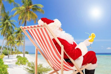 Santa Claus lying on a chair and drinking orange cocktail
