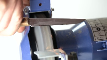 Sharpening kitchen knife on grindstone