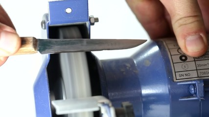 Sharpening kitchen knife on grindstone