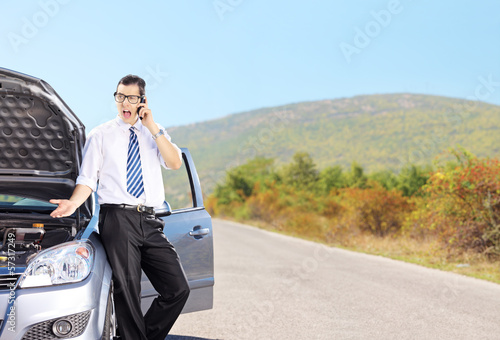Nervous male standing next to his car and talking on a phone