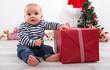 Baby mit einem Geschenk zu Weihnachten in Rot