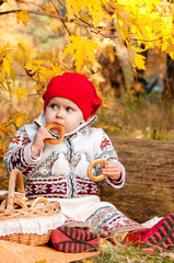 Cute little baby girl sitting in the forest and eating a bagel