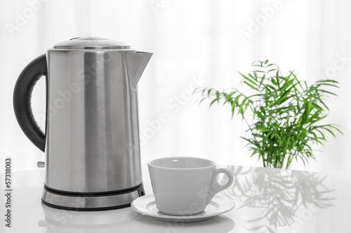 White cup and electric kettle on the table