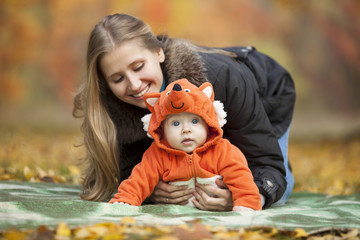 Young woman with baby dressed in fox costume in autumn park