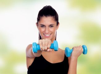 Brunette girl with blue dumbbells toning her muscles