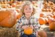Little Boy Sitting and Holding His Pumpkin at Pumpkin Patch.