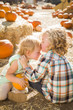 Sweet Little Boy Kisses His Baby Sister at Pumpkin Patch.