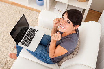 Excited Young Woman Sitting With Laptop