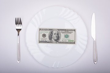 One hundred dollar bill lies on white plate with knife and fork