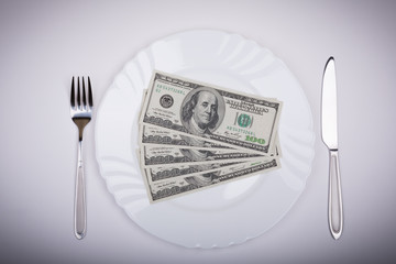 One hundred dollar bills lie on white plate with knife