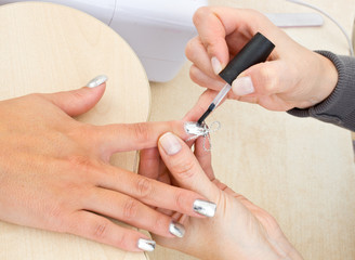 beautician polishing woman nails