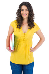 Happy curly haired student holding notebooks