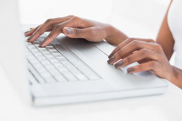 Close up on womans hands using her laptop