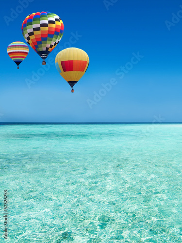 Hot air balloons travel over the sea