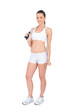 Peaceful fit sportswoman holding skipping rope around neck