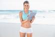 Smiling slender blonde in sportswear using tablet