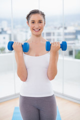 Cheerful sporty brunette exercising with dumbbells