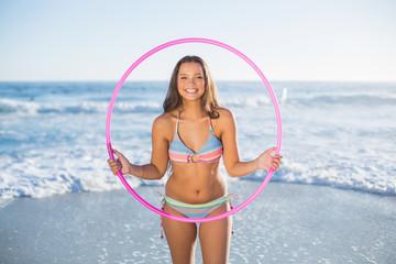 Cheerful attractive woman in bikini playing with hula hoop