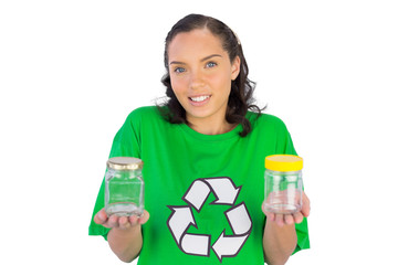 Wondering woman wearing green shirt with recycling sign holding