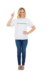 Cheerful blonde volunteer pointing up