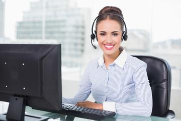 Cheerful brunette businesswoman using headset