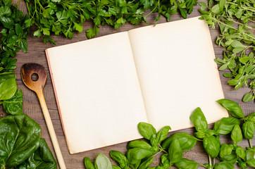 Buch für Rezept mit Kochlöffel und Kräuter