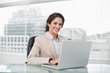 Happy businesswoman typing on laptop at her desk looking at came