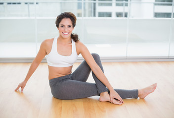 Sporty cheerful smiling brunette stretching on the floor