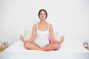 Serene young brown haired model in white pajamas practicing yoga