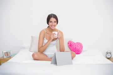 Pleased young brown haired model in white pajamas enjoying a cof
