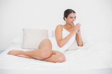 Calm young brown haired model in white pajamas drinking coffee