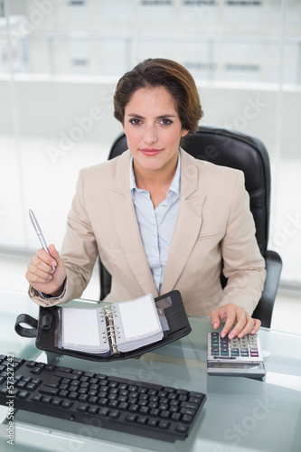 Businesswoman using calculator and diary looking at camera