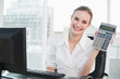 Happy businesswoman showing calculator sitting at desk